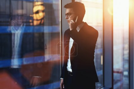 Photo for Portrait of successful businessman talking on mobile phone while standing against window in hallway of modern office interior, young confident man having cell telephone conversation during work break - Royalty Free Image