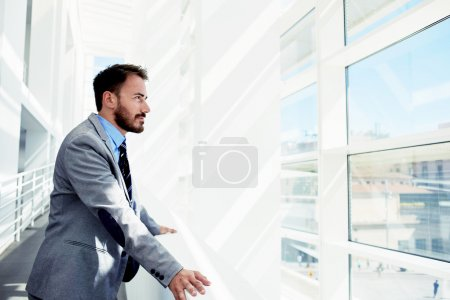 Photo for Portrait of a serious man office worker dressed in elegant clothes watching in window while standing in modern office space, thoughtful young male entrepreneur in suit resting after business meeting - Royalty Free Image