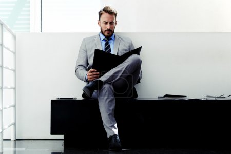 Photo for Portrait of a confident man entrepreneur studying important paper documents before business meeting, young seroius male dressed in elegant suit reading his portfolio before interview with employer - Royalty Free Image