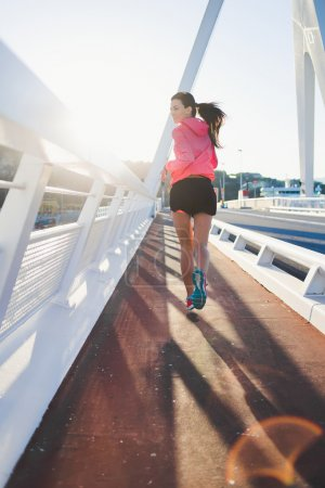 Athletic woman running on the bridge