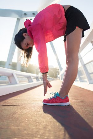 Woman runner stretching legs muscles