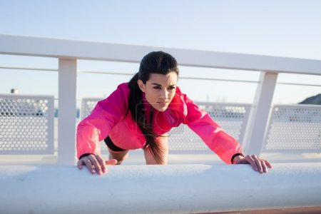Fit woman doing push-ups exercises
