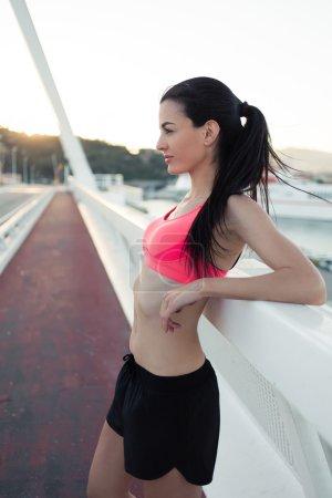 Photo pour Portrait d'une femme fatiguée joggeuse avec une silhouette parfaite se reposant après une course active dans l'air frais pendant le temps libre, jeune femme athlétique rêveuse se relaxant après l'entraînement de fitness en plein air en soirée d'été - image libre de droit