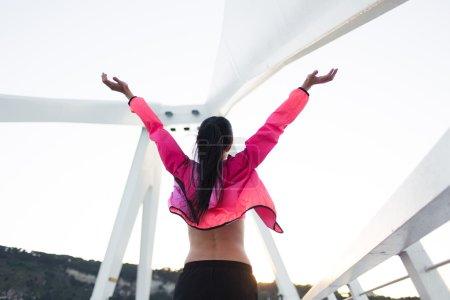 Photo pour Vue arrière d'une femme en forme avec un corps mince debout avec les mains levées abattant la liberté pendant le repos après l'entraînement, jeune femme heureuse profitant d'une bonne soirée et le temps après l'entraînement dans l'air frais - image libre de droit