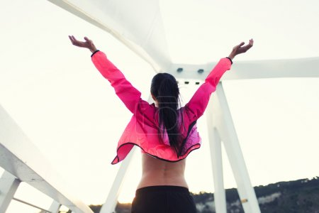 Sportswoman raised hands with feeling of freedom