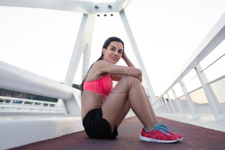 Photo pour Portrait de femme fatiguée mais satisfaite de la formation de fitness athlétique assise et se reposer après l'entraînement à l'extérieur, jeune femme sportive magnifique profitant du repos et bonne soirée après l'exercice physique à l'extérieur - image libre de droit