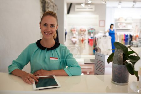 Woman working on touch pad in store