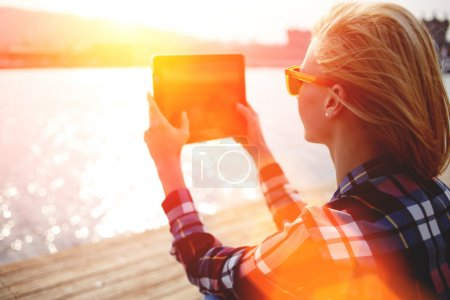 Photo for Young stylish hipster girl photographing on digital tablet beautiful sea landscape in summer evening, woman taking photo with touch pad camera while sitting on a river jetty during recreation time - Royalty Free Image