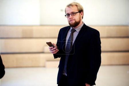Photo pour Portrait à mi-longueur d'un jeune avocat masculin intelligent en tenue formelle tenant son téléphone portable dans le couloir du bureau, homme d'affaires confiant utilisant un téléphone portable tout en se reposant après la conférence - image libre de droit