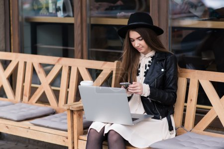 Portrait of a young beautiful woman dressed in with style using mobile phone during work on portable laptop computer, female freelancer chatting on cell telephone while sitting with net-book outdoors