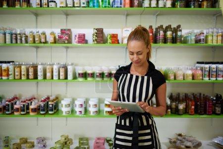 Foto de Retrato de una empresaria próspera que usa almohadilla táctil para comprobar el número de productos cosméticos, joven consultora que sostiene la tableta digital mientras está de pie contra estantes con productos de spa - Imagen libre de derechos
