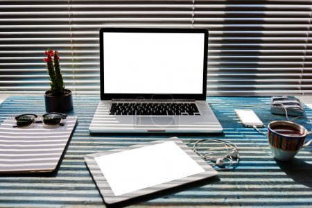 Foto de Escritorio moderno con accesorios y herramientas de trabajo a distancia, computadora portátil, teléfono móvil y tableta digital con pantalla de espacio de copia en blanco para su contenido, carga de teléfono celular, bloc de notas y taza de té - Imagen libre de derechos