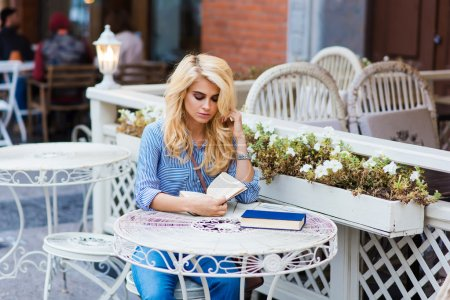 Attractive blonde lady reading book