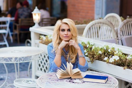 Attractive young woman sitting with books