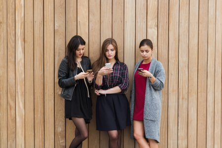 Three women chatting on mobile phones