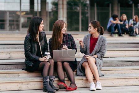 Photo pour Groupe de hipster jeunes filles ou des jeunes filles parler les uns aux autres tout en restant assis avec net-book portable sur un campus, arbre femmes avec look cool discuté d'un sujet pendant le travail sur ordinateur portable - image libre de droit