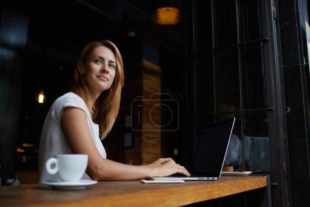 Photo pour Belle femme de race blanche, rêvant quelque chose tout en restant assis avec portable net-book au bar café moderne, jeune charme féminin pigiste penser de nouvelles idées lors de travaux sur ordinateur portable - image libre de droit