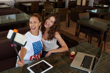 Photo pour Filles de hipster gai posant alors qu'elle photographiait eux-mêmes pour photo réseau social pendant le déjeuner Rodez café, femmes heureux faire photo avec caméra de téléphone intelligent via clé libre assis dans bar - image libre de droit