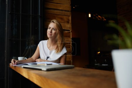 Charming blonde woman reading magazine