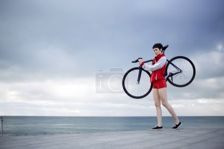 Female rider holding her sports bicycle