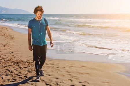 Young sportsman walking along on seashore