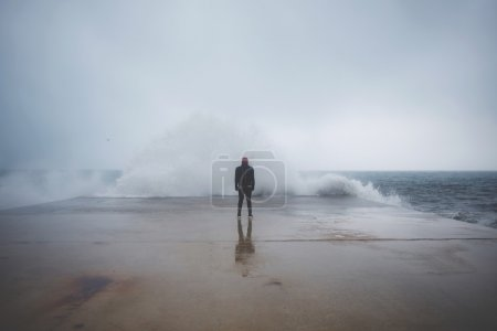 Photo for Feeling of freedom, back view of adult man standing on pier facing to the sea with big waves beats against the shore on a cloudy autumn day, alone depress person,the power of nature, storm on seashore - Royalty Free Image