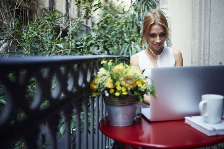 Woman working on laptop computer at balcony