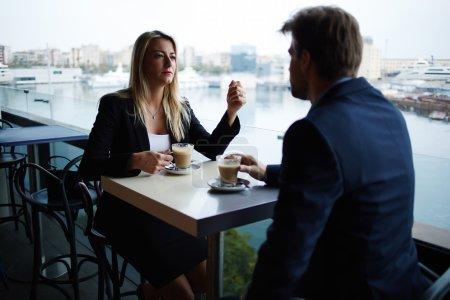 Photo pour Couples de dirigeants influents réussis ayant la discussion de réunion tandis qu'ils boivent le café, les gens d'affaires parlant les uns aux autres pendant la coupure de café dans l'endroit moderne de luxe avec la vue de port de marina de mer - image libre de droit