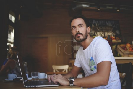 Male developer comes up with ideas for website while sitting front open laptop computer in cozy restaurant interior, young man thinking about something during work on net-book in modern coffee shop