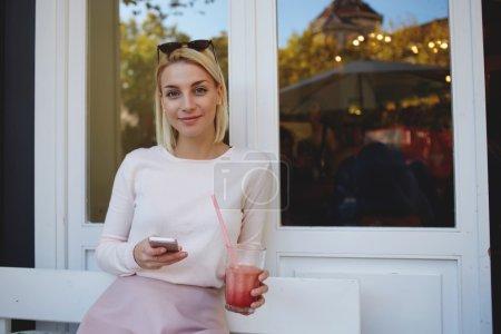 Foto de Bastante joven mujer utilizando el teléfono móvil mientras estaba sentado en la acera acogedor café - Imagen libre de derechos