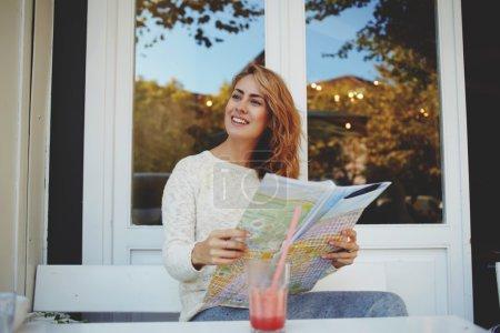 Photo pour Jeune femelle voyageur explorant la carte tout en se reposant dans café trottoir moderne - image libre de droit