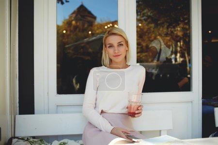 Foto de Mujer rubia encantadora esperando una llamada en el teléfono móvil mientras disfruta el jugo fresco en café acogedor - Imagen libre de derechos