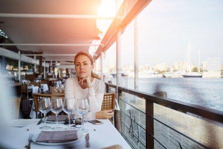 female tourist sitting in sidewalk cafe