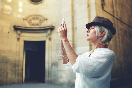 Foto de Cuadro de toma de moda joven en teléfono móvil estando cerca de un monumento arquitectónico en escena urbana - Imagen libre de derechos