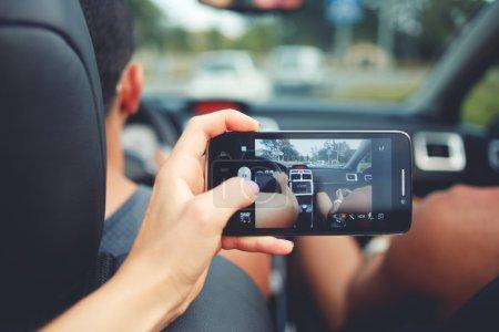 Photo pour Vue prise de vue recadrée de la main d'une femme faisant la photo sur son téléphone portable alors qu'elle était assise sur le siège arrière d'une voiture de luxe cabriolet - image libre de droit