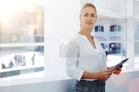 Photo pour Jeune entrepreneur réussi tenant tablette numérique dans les mains tout en se tenant dans l'intérieur de bureau moderne - image libre de droit