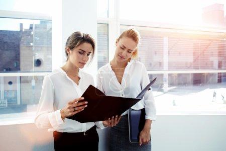Photo pour Équipe des femmes d'affaires réussis compte tenu des documents papier en se tenant debout à l'intérieur de bureau moderne - image libre de droit