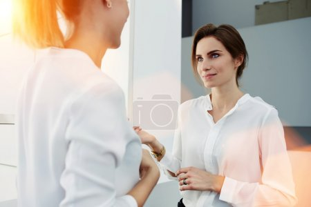 Two businesswomen having pleasant conversation