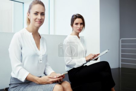 Businesswomen with digital tablet and cell telephone
