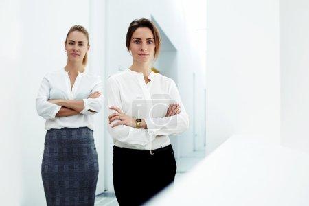 Photo pour Équipe de femmes ayant réussi debout dans l'intérieur de bureau moderne après avoir rencontré de clients - image libre de droit