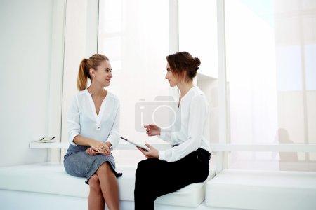 two women sitting in modern office