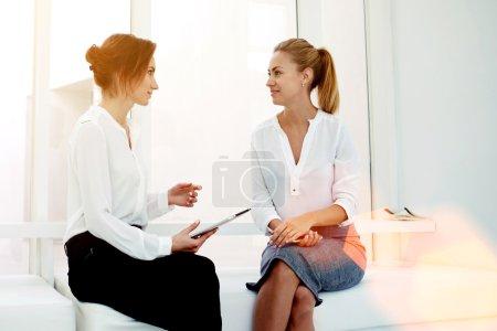 Foto de Joven empresario hold teclado mientras que dice algo a su compañero durante la reunión de negocios, dos ceos orgullosa confianza mujer discutiendo el nuevo proyecto sentado en el interior de la oficina moderna - Imagen libre de derechos