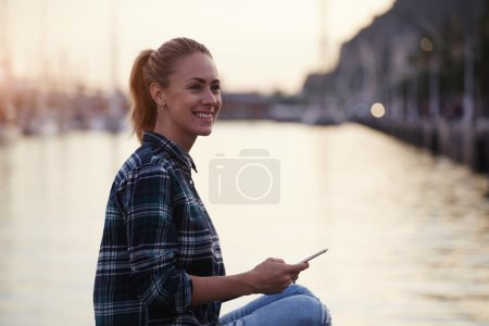 Photo for Happy young hipster girl looking away while sitting with mobile phone in beautiful summer evening near sea port, cheerful happy woman holding cell telephone and smiles to her friends which she saw - Royalty Free Image