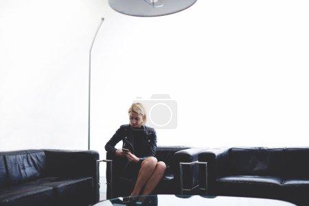 Photo pour Affichage de photos féminines à la mode sur téléphone portable tout en étant assis sur fond blanc avec un espace de copie pour le message texte ou le contenu d'information, femme bavarder sur le téléphone portable dans le studio moderne - image libre de droit