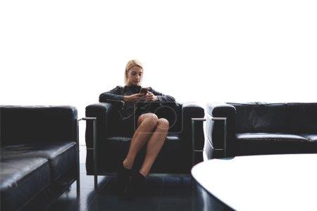 Photo pour Femelle avec style cool est le chat dans les réseaux sociaux via téléphone portable tout en restant assis dans la salle d'attente à l'intérieur, séduisante blonde cheveux femme lecture de SMS sur téléphone portable pendant le temps libre - image libre de droit