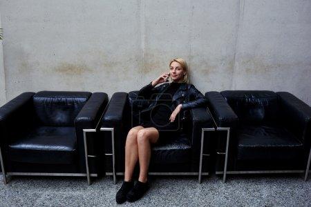 Photo pour Fille de hipster élégant téléphoner via téléphone portable tout en restant assis sur un canapé en cuir noir intérieur studio moderne, femme au look branché, parler au téléphone portable pendant que vous attendez de rencontrer des amis - image libre de droit