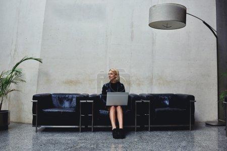 Photo pour Jeune femme, pensez à quelque chose assis avec net-livre ouvert en studio moderne intérieur - image libre de droit