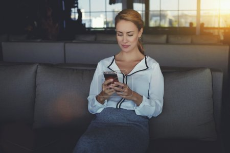 Photo pour Le message texte d'écriture femelle sur son téléphone portable tout en se détendant dans le café après jour de travail, jeune femme se connecte à l'Internet par l'intermédiaire du téléphone portable tout en attendant dans le restaurant ses associés d'affaires - image libre de droit