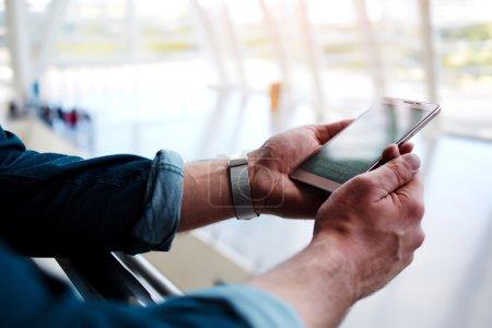 Photo pour Coupé vue prise de vue des mains d'un homme tenant un téléphone cellulaire tout en se tenant dans le centre commercial, jeune homme se connectant au sans fil via téléphone mobile en attendant quelqu'un dans le hall de l'aéroport moderne - image libre de droit