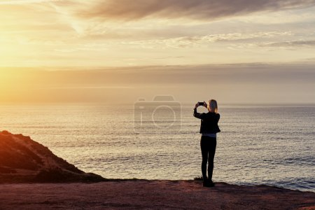 Photo pour Young woman traveler shoots video on smart mobile phone of a beautiful sunset above the sea, hipster girl taking photo of amazing ocean landscape on cell telephone during her autumns adventure - image libre de droit
